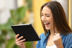 Excited woman checking news on tablet in the street stock photo