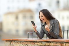 Excited woman checking smart phone in a balcony. With a town in the background royalty free stock image