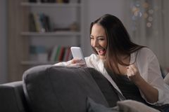 Excited woman checks smart phone in the night at home royalty free stock image
