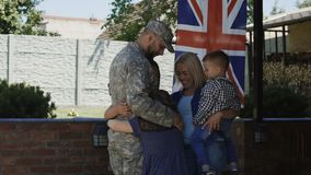 Loving family meeting soldier back at home. Excited woman with children welcoming serviceman back at home embracing and laughing happily against British flag stock video
