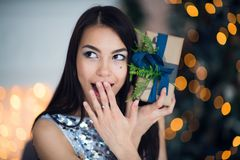 Excited woman in Christmas night sitting near tree and lifting her Christmas gift to listen what`s inside.  stock photos