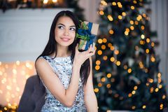 Excited woman in Christmas night sitting near tree and lifting her Christmas gift to listen what`s inside.  Royalty Free Stock Images