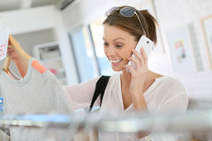 Excited woman about the clothing sumer sales talking on the phone Royalty Free Stock Photos
