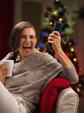 Excited woman with cup of beverage looking TV Royalty Free Stock Photography