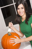 Excited Woman Cutting Carving Halloween Pumpkin Jack-O-Lantern Royalty Free Stock Photography