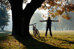 Excited woman cyclist. Standing in a park with hands outstretched embracing vitality freedom. Near the tree is a bicycle. Outdoor Royalty Free Stock Photo