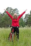 Excited woman cyclist with hands outstretched Stock Images