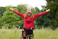 Excited woman cyclist with hands outstretched Royalty Free Stock Photos