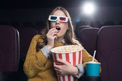 Excited woman in 3d glasses eating popcorn and watching movie. In cinema royalty free stock photos