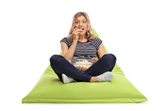 Excited woman eating popcorn on beanbag royalty free stock images