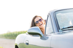 Excited woman enjoying road trip in convertible against clear sky Stock Images