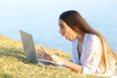 Excited woman finding on line offers in a laptop on the grass. Side view portrait of an excited woman finding on line offers in a laptop lying on the grass Royalty Free Stock Photography