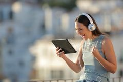 Excited woman finding media offer on a tablet. Excited woman finding media offers on a tablet sitting in a town at sunset royalty free stock photography