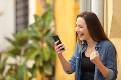 Excited woman finding online offers on a smart phone royalty free stock image