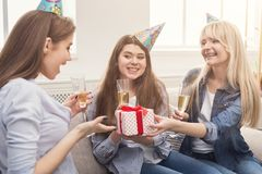 Excited woman getting gift from her friends. Excited women getting present from her friends in caps. Birthday, holidays, celebration and female friendship Stock Photography