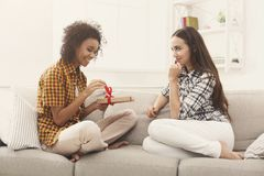 Excited woman getting gift from her girlfiend. Excited women getting gift from her girlfriend. Two happy female friends exchanging presents, copy space Royalty Free Stock Photography