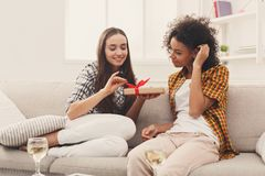 Excited woman getting gift from her girlfiend. Happy girls exchanging gifts. Excited women getting present from her friend. Birthday, holidays, celebration and Royalty Free Stock Photo