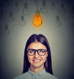 Excited woman in glasses looking up at bright light bulb above head has an idea Royalty Free Stock Images
