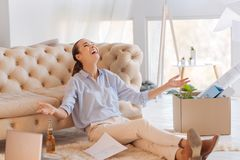 Emotional young woman looking excited while being at home. Excited woman. Happy young cheerful woman sitting on the floor with her head leaning back and smiling Royalty Free Stock Photos