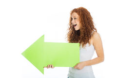 Excited woman holding an arrow pointing left. A happy, excited woman looking at something and pointing to the left with a green arrow Royalty Free Stock Photo