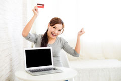 Excited woman holding credit card with notebook computer Stock Images