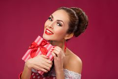 Excited Woman Holding Gift Box. Pin-up retro style Stock Image