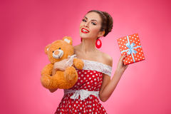Excited Woman Holding Gift Box and Teddy Bear Stock Photo