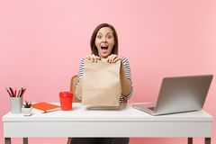 Excited woman holding in hand brown clear empty blank craft paper bag work at office with laptop isolated on pink. Background. Food products delivery courier royalty free stock photography