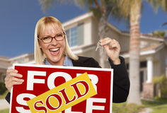 Excited Woman Holding House Keys and Sold Real Estate Sign. In Front of Nice New Home royalty free stock image