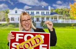 Excited Woman Holding House Keys and Sold Real Estate Sign Royalty Free Stock Photography