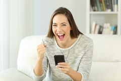 Excited woman holding phone looking at you. Front view portrait of an excited woman holding phone looking at you sitting on a sofa in the living room of a house Stock Photos
