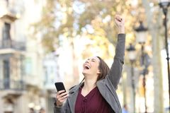 Excited woman holding phone and raising arm in the street. Portrait of an excited woman holding smart phone and raising arm in the street royalty free stock photos