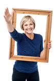 Excited woman holding picture frame Royalty Free Stock Images