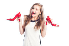 Excited woman holding red shoes Royalty Free Stock Images