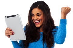 Excited woman holding touch pad Stock Photo