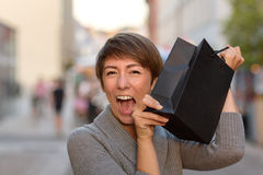 Excited woman holding up a boutique bag Royalty Free Stock Image