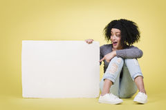 Excited woman indicating a white paper board. Stock Photos