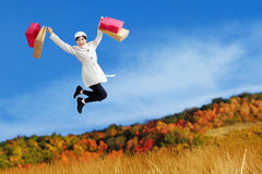 Excited woman jump with shopping bags Stock Photos