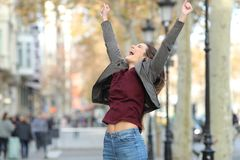 Excited woman jumping in the street royalty free stock image