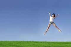 Excited woman jumping over blue sky Royalty Free Stock Photo