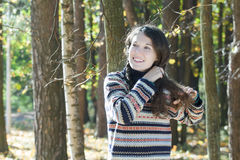 Excited woman in knitted woolly sweater doing braid Stock Photography