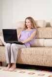 Excited woman with laptop. Young blonde woman is sitting on sofa with laptop Stock Photos