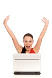 Excited woman with laptop. Girl with laptop raising her arms in joy Royalty Free Stock Photography