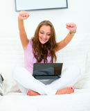 Excited woman with laptop on sofa rejoicing succes. Excited woman sitting on sofa at home with laptop and rejoicing her success Royalty Free Stock Image