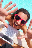 Excited woman with laptop waving hands at poolside. Portrait of excited young Caucasian woman wearing sunglasses waving hands at poolside with laptop by her Stock Images