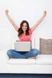 Excited Woman With Laptop. Excited Young Woman Sitting On Couch With Laptop Stock Image