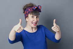 Excited woman laughing with thumbs up for cool success Royalty Free Stock Images