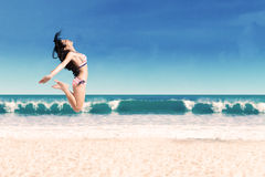 Excited woman leaping at beach Stock Images