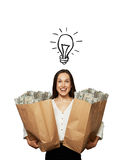 Excited woman with light bulb. Excited young woman with drawing light bulb holding paper bags with money over white background Stock Photography