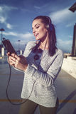 Excited woman listening music at parking house in downtown Royalty Free Stock Photography